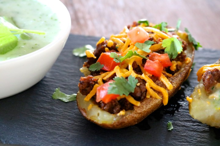 Taco Potato Skins | Crispy paleo potato skins stuffed with taco meat, dairy free cheese, and tomatoes. Served with a dairy free jalapeno cilantro yogurt sauce for dipping. | eatsomethingdelicious.com