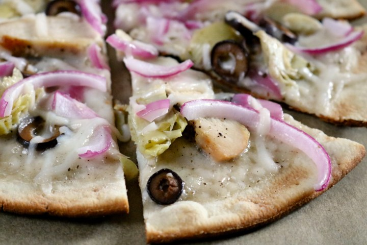 Grilled Pizza | Learn how to cook a pizza on a grill for an extra crispy crust. This gluten and dairy free pizza is topped with alfredo sauce, grilled chicken, and veggies. | eatsomethingdelicious.com