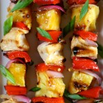 Three skewers of grilled chicken, vegetables, and pineapple topped with sauce and scallion slices.