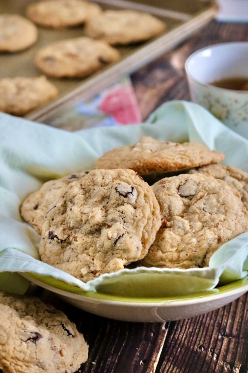 Chocolate chip cookies in a linen lined bowl. An out of focus background shows a cup of tea and additional cookies on a baking sheet all on a wood background.