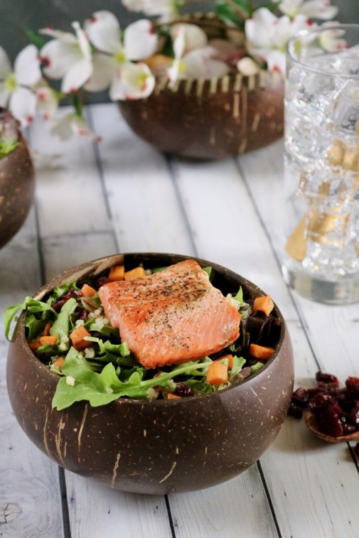 Salmon salad with a glass of water and bowl of flowers behind it.