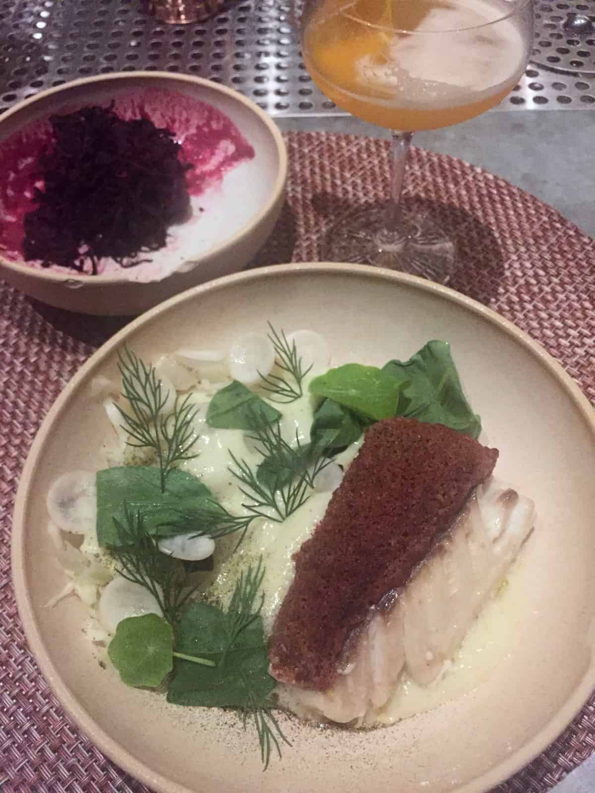 Piece of fish with greens and a bowl of beets and a cocktail in the background
