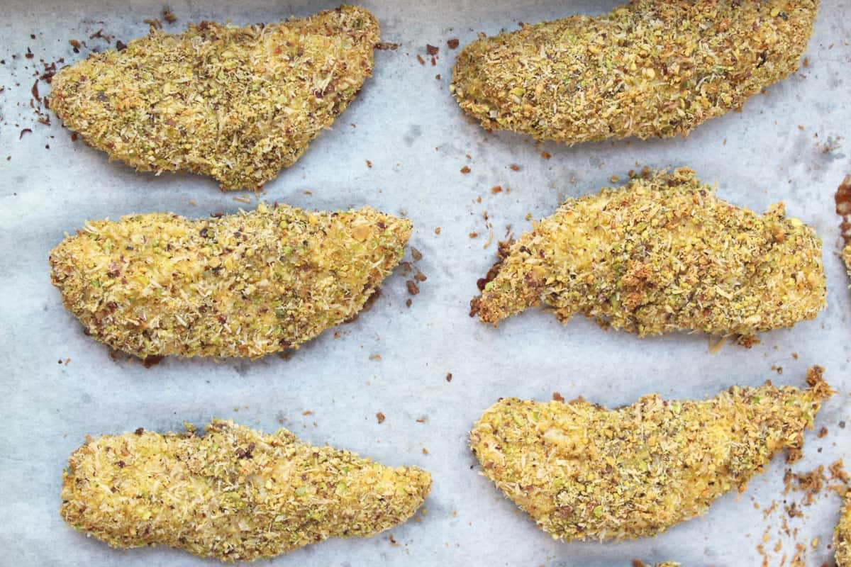 A healthy alternative to standard chicken fingers, these Pistachio Coconut Baked Chicken Tenders have only a handful of ingredients making them gluten free, paleo, and Whole30 approved! - Eat the Gains