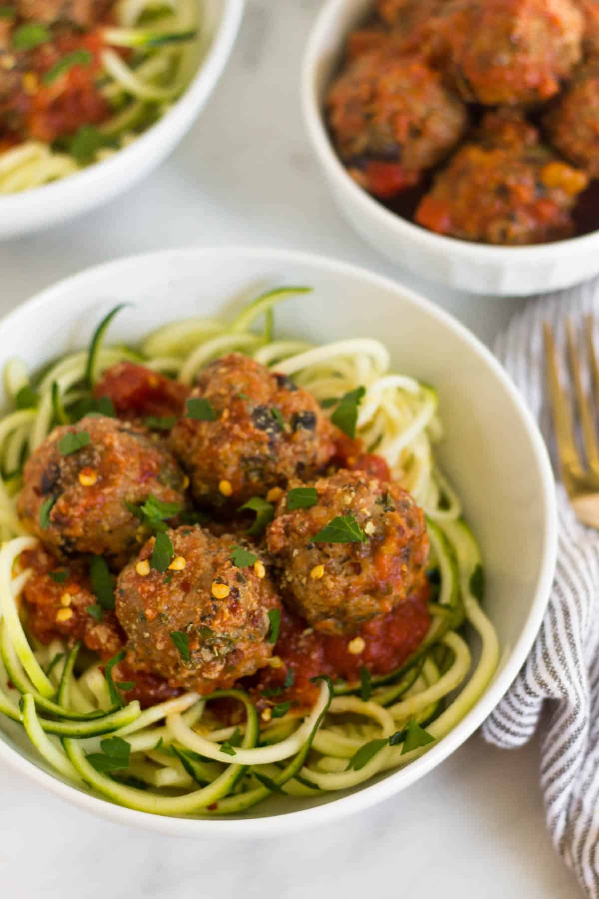 Bowl of zucchini noodles and supreme pizza meatballs with a smaller bowl of meatballs and sauce and another bowl of zucchini noodles in the background