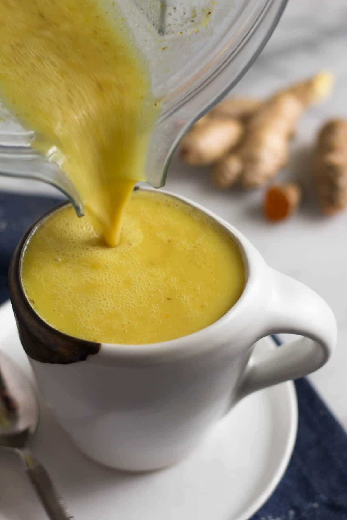 Golden milk turmeric latte being poured into a white mug on top of a plate