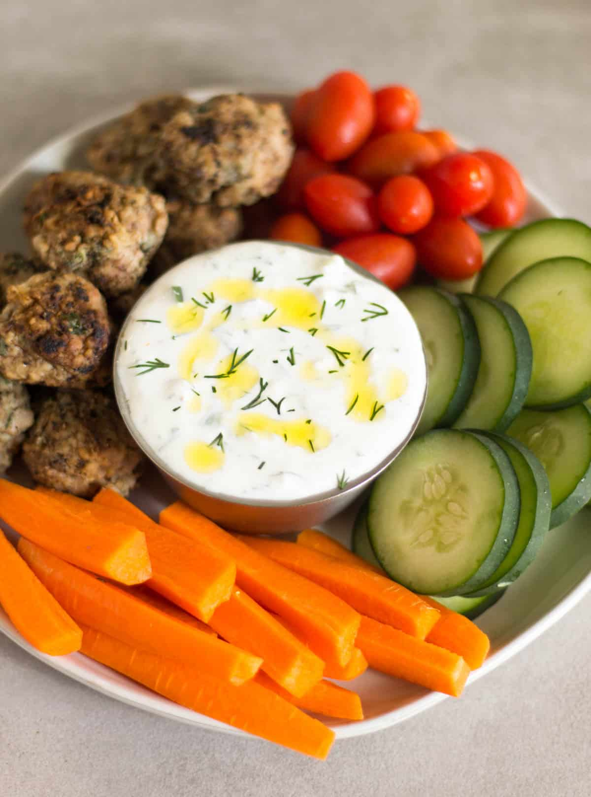 Homemade tzatziki surrounded by fresh veggies and meatballs all on a plate
