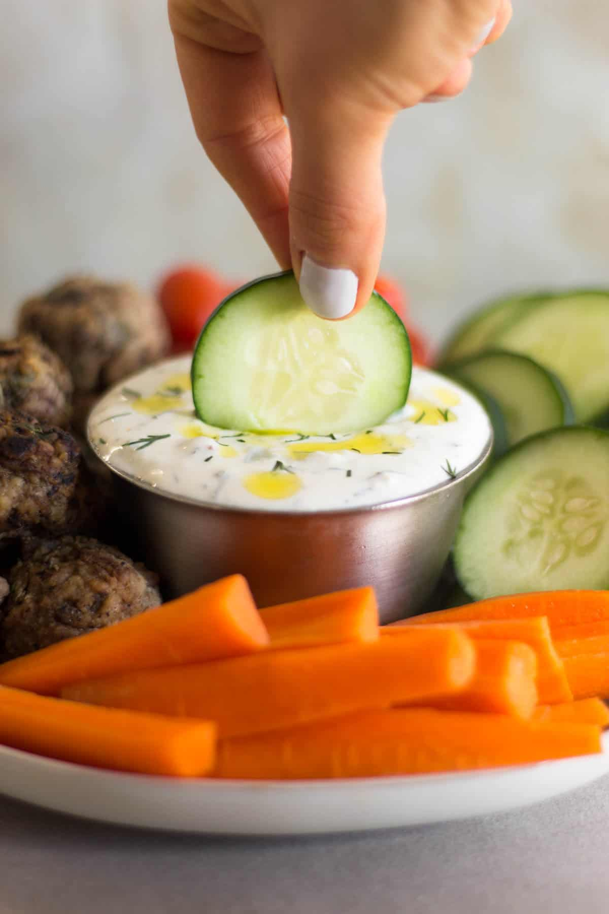 Cucumber being dipped into homemade tzatziki sauce surrounded by veggies and meatballs