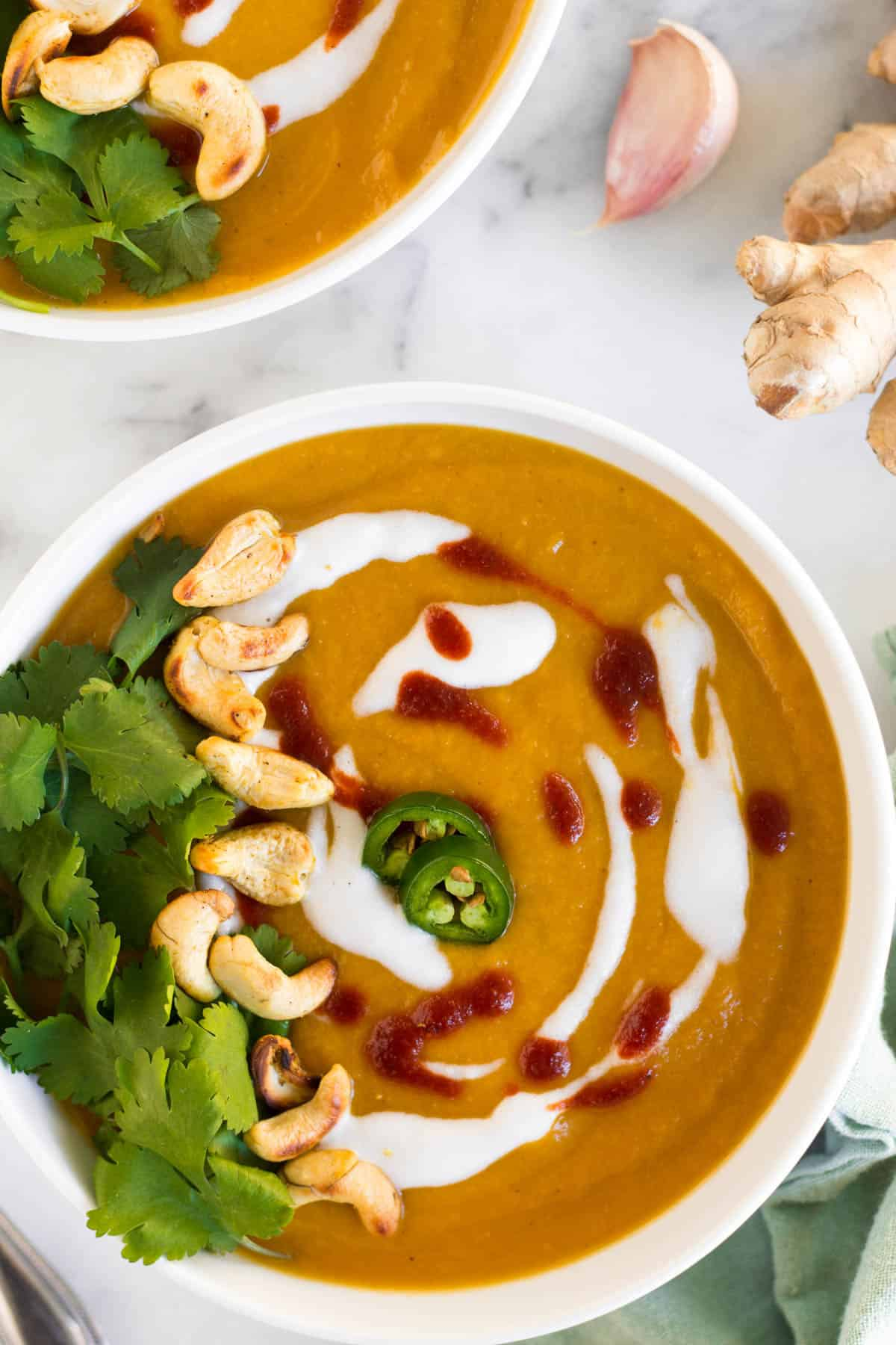Curry Cauliflower Butternut Squash Soup in a white bowl with toppings
