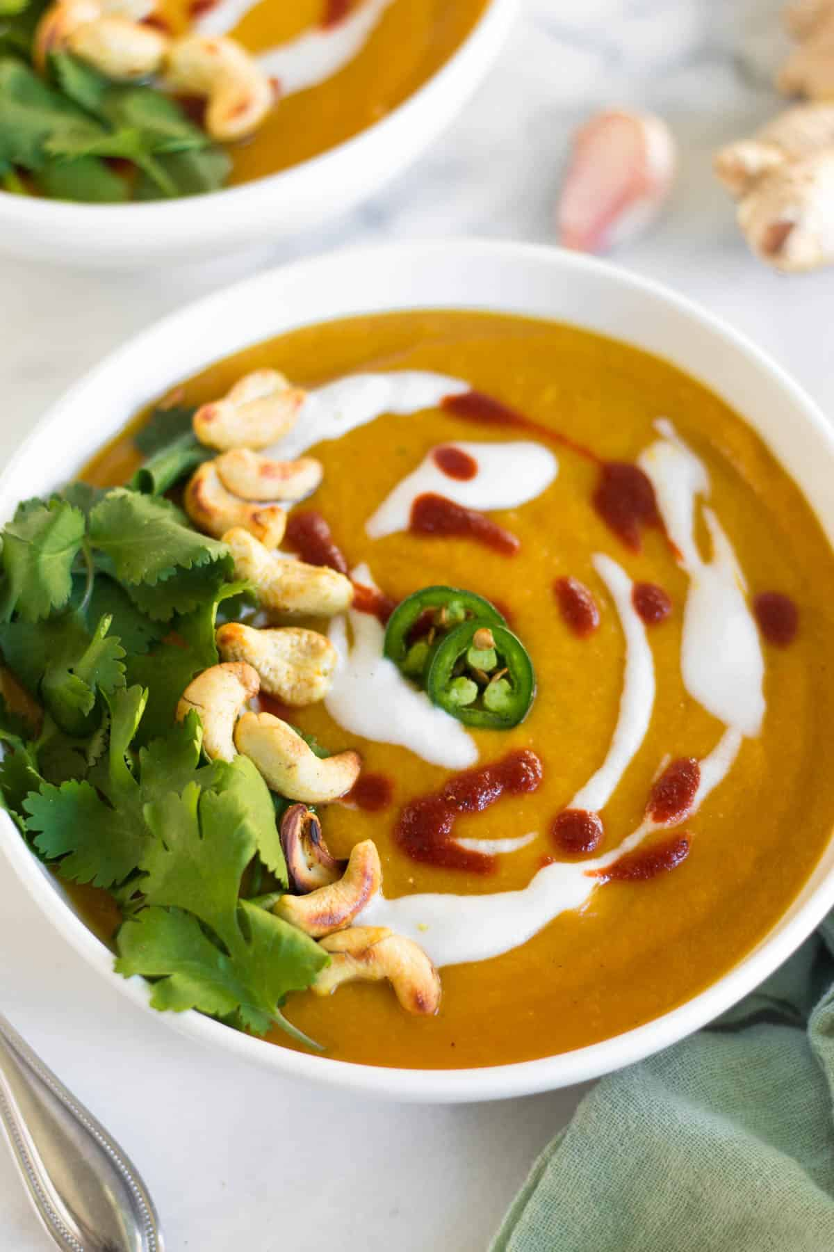 White bowl on a marble counter with curry cauliflower butternut squash soup garnished with cilantro, cashews, coconut yogurt, hot sauce, and jalapeños