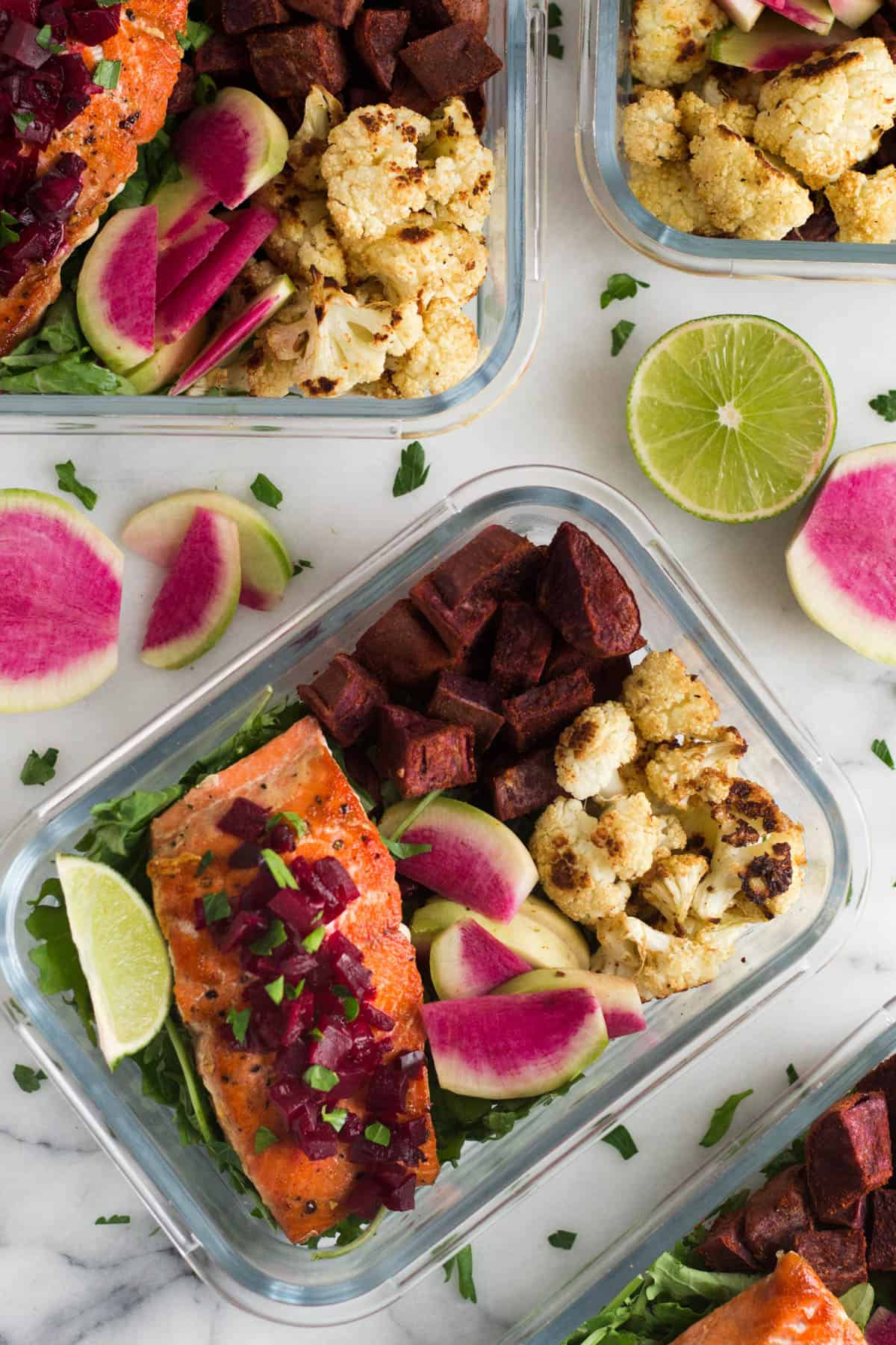Multiple glass meal prep container filled with salmon and veggies on a white counter with limes and radishes on it