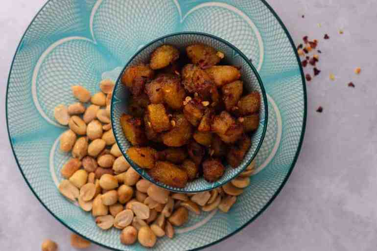 Kelewele | Spicy fried plantain in a bowl with some peanuts on the side