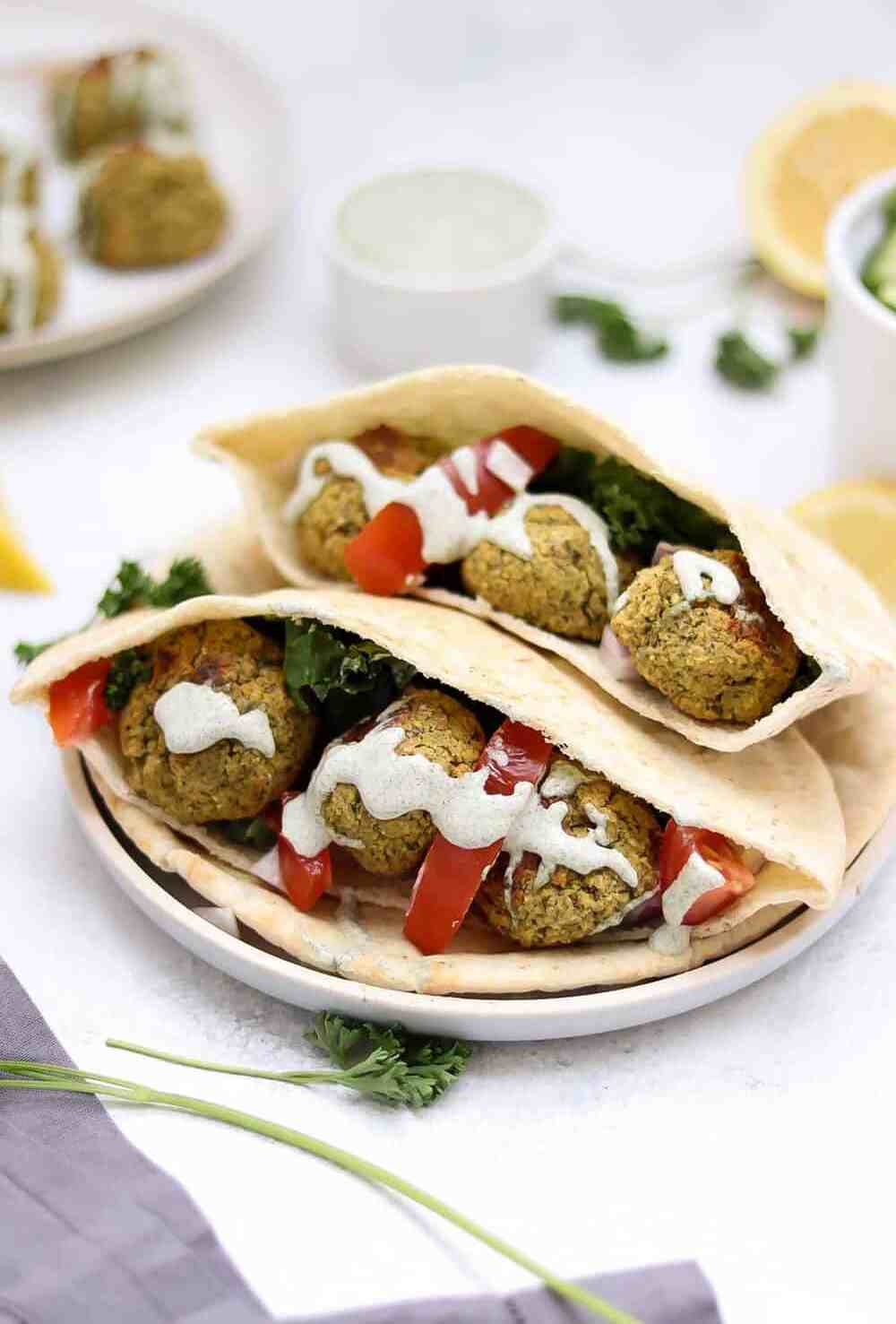 Baked falafel recipe pictured with pita, creamy dill dressing, and fresh cilantro.