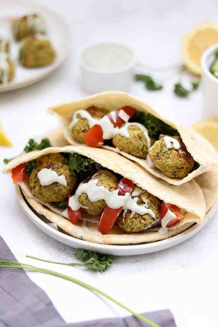 Falafel pictured with pita bread, creamy dill dressing, and fresh cilantro.