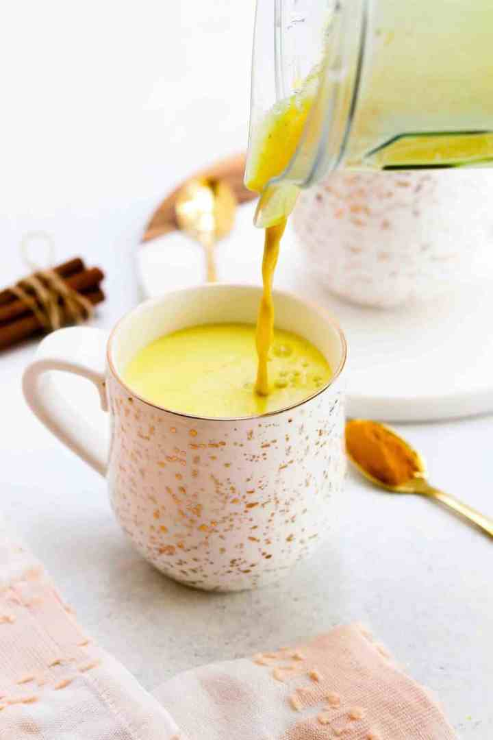 Turmeric golden milk latte pouring into a gold speckled mug with cinnamon sticks.