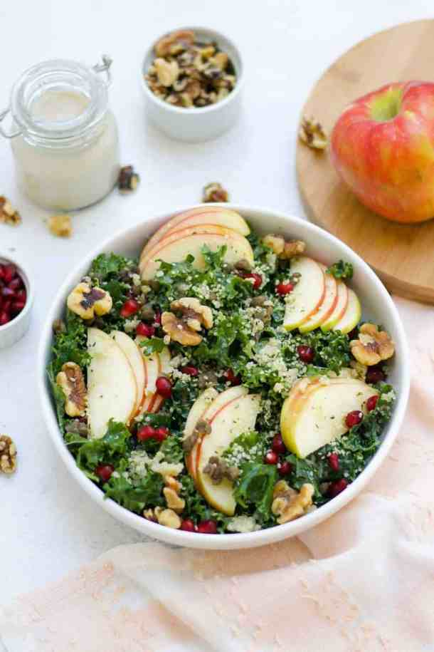 Easy chopped kale salad with sliced apples in a white bowl.