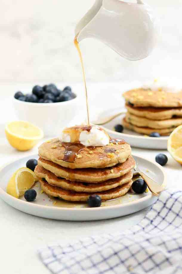 Four pancakes stacked on a blue plate with maple syrup pouring on top.