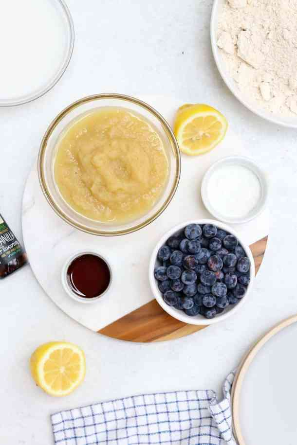 Ingredients for the lemon blueberry pancakes lined up in white and glass circle bowls.