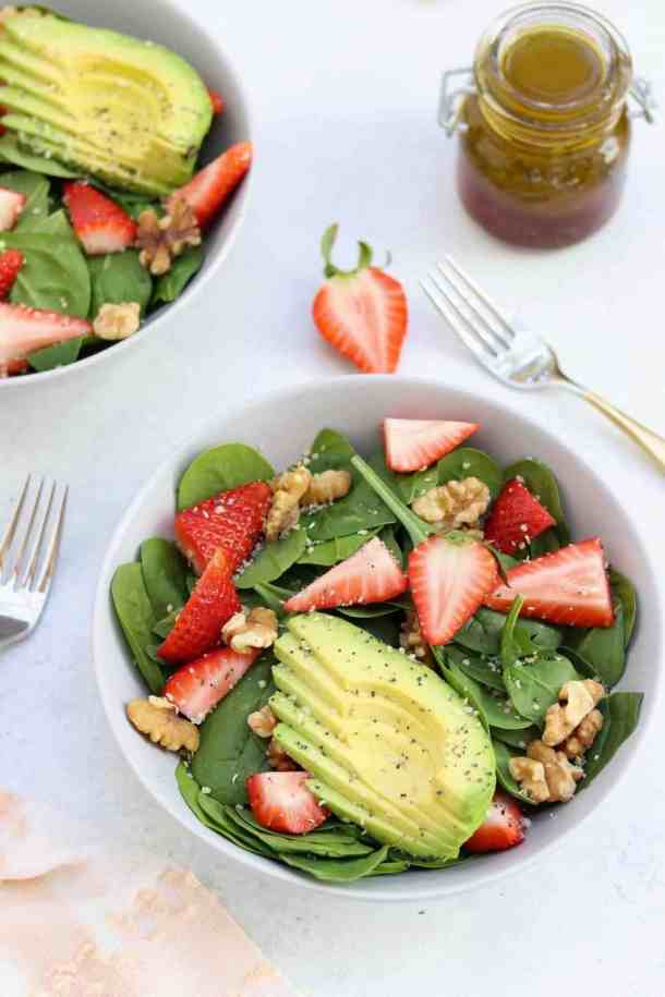 overhead shot with two bowls strawberry spinach salad with forks on the side.