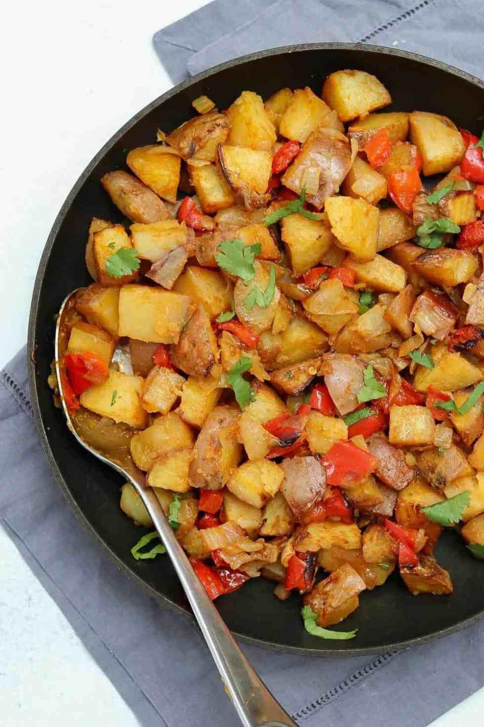 Crispy roasted breakfast potatoes in a black skillet on a grey napkin.