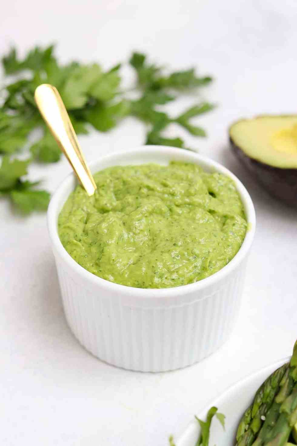 Green goddess dressing in a white bowl with a gold spoon resting inside.