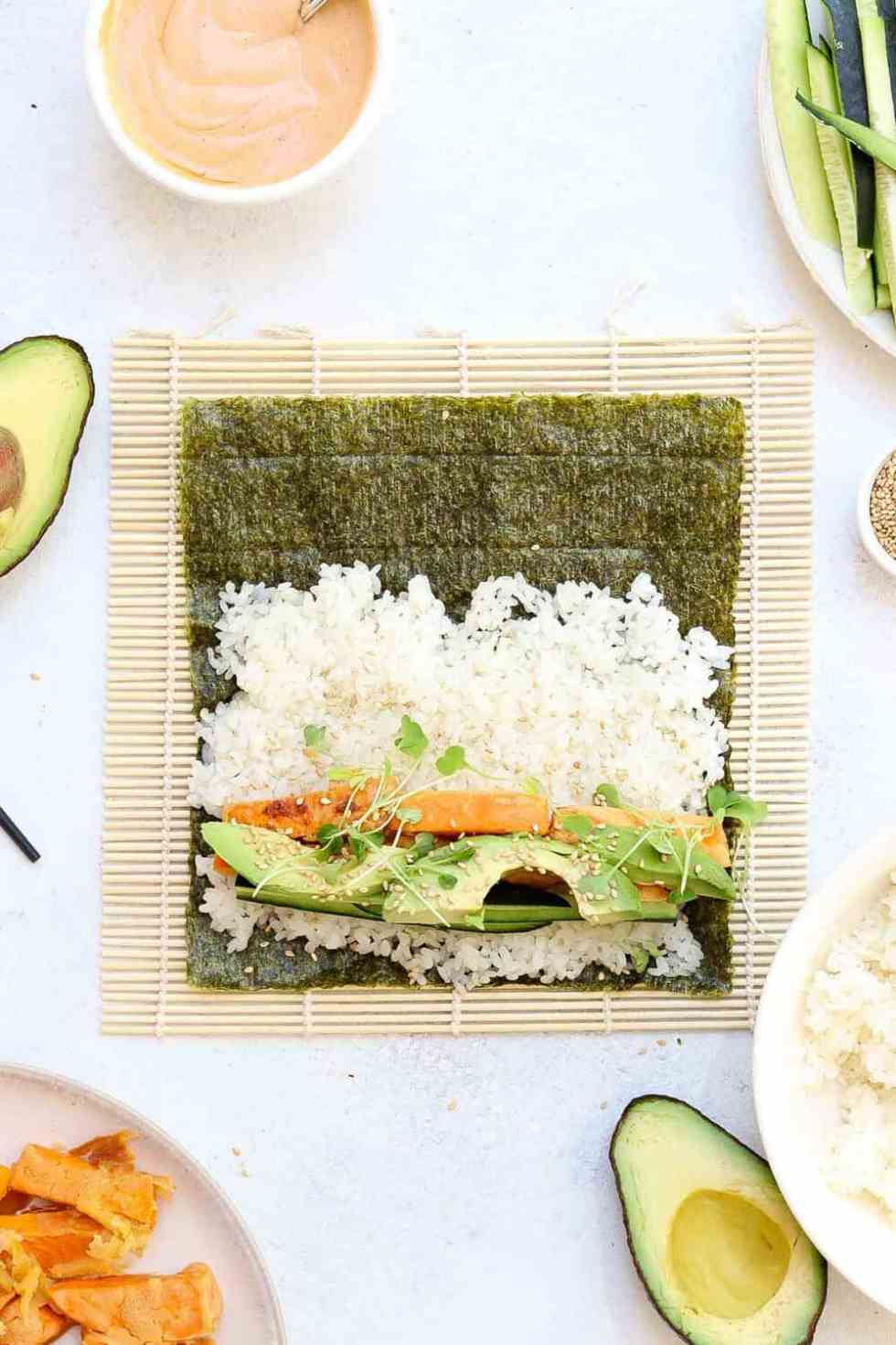 Avocado and sweet potato on top of white rice and nori ready to be rolled up.