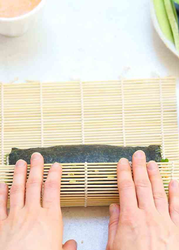 Using a bamboo mat to roll the vegetarian sushi roll.