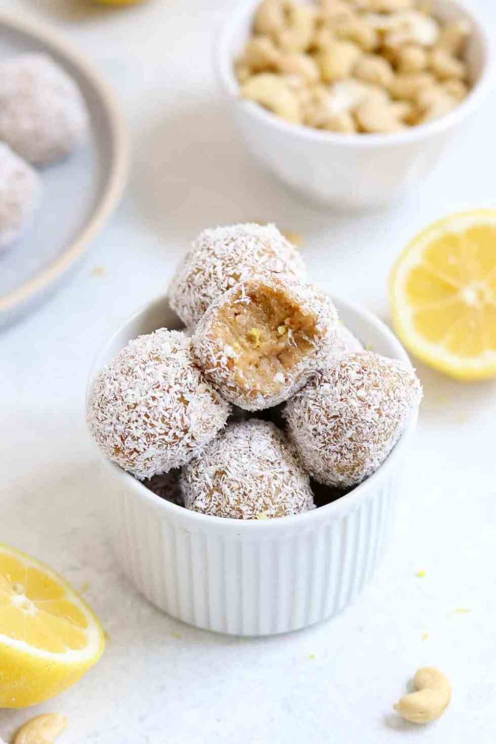 Pile of bliss balls in a white bowl with cashews and lemon in the background.