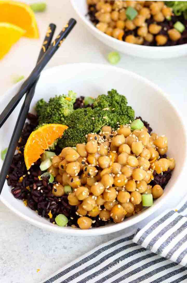 Up close of orange chickpeas in a white bowl with black rice and chopsticks.