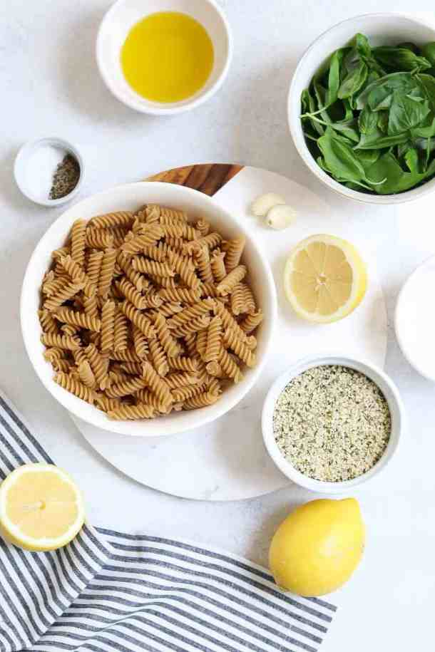 Ingredients for vegan pesto pasta arranged on a white backdrop.