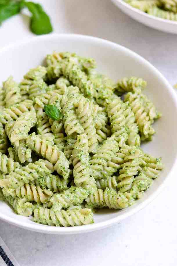 Up close shot of pesto pasta in a white bowl with basil on top.