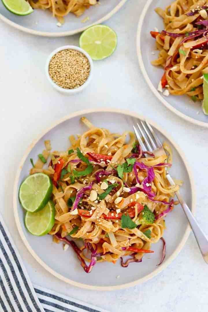 Thai noodle salad on a small blue plate with a fork on the right side.