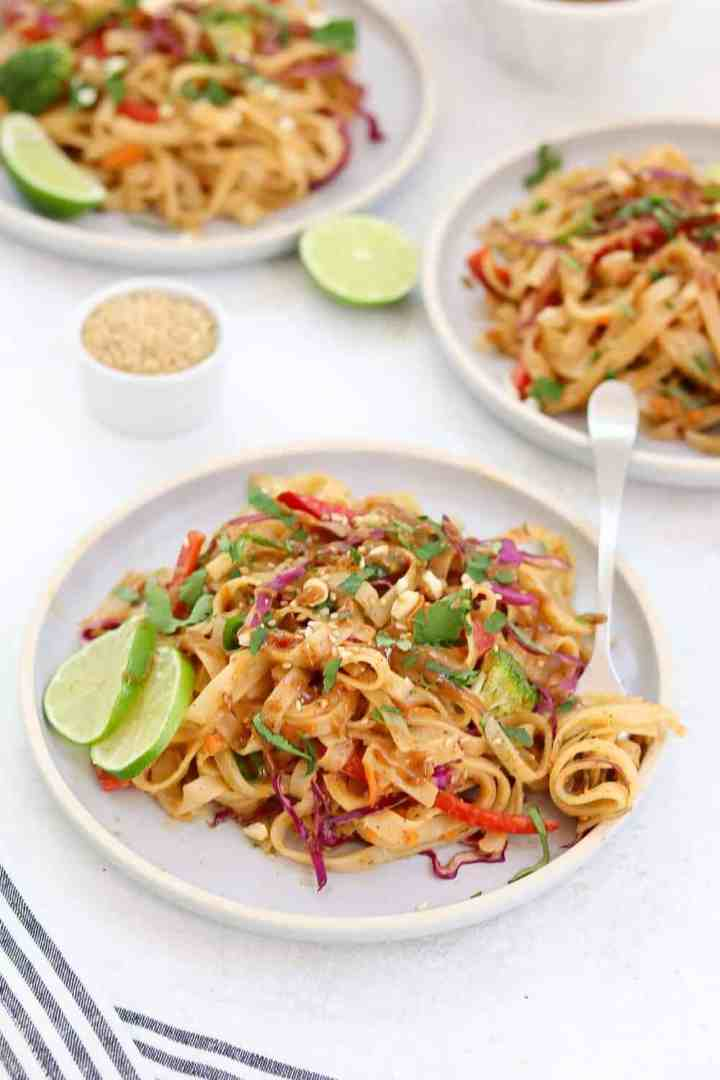 Three blue plates with thai noodle salad and lime wedges on the side.