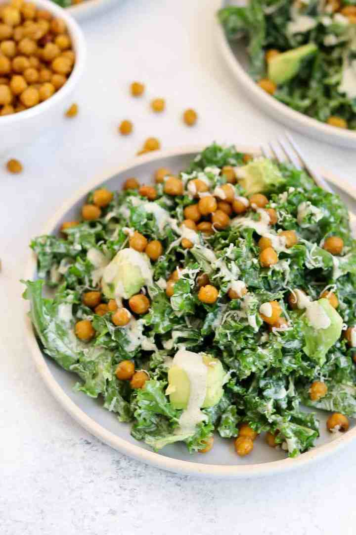 Up close of kale caesar salad on a small blue plate with dressing drizzled on top.