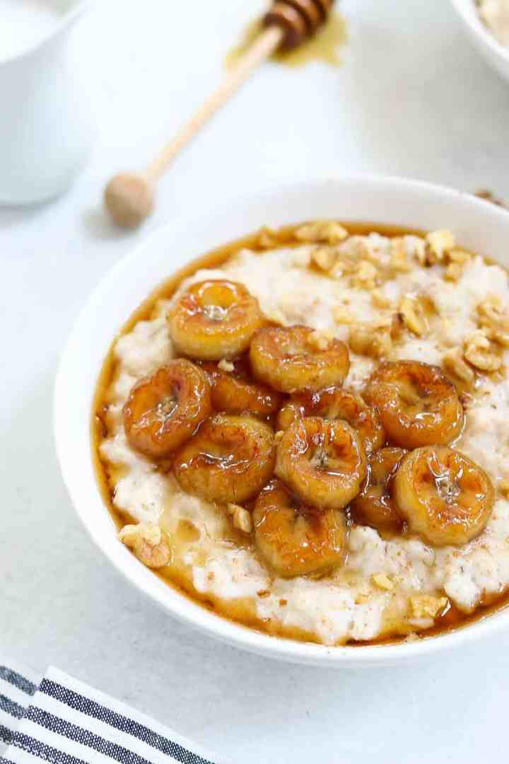 Up close image of caramelized banana oatmeal in a white bowl with maple syrup on top.
