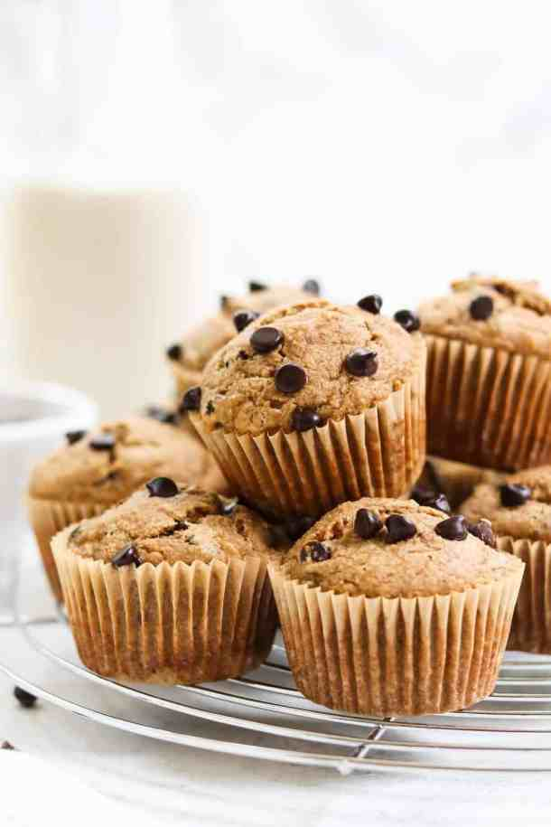 A pile of muffins stacked on top of each other on a silver cooling rack.