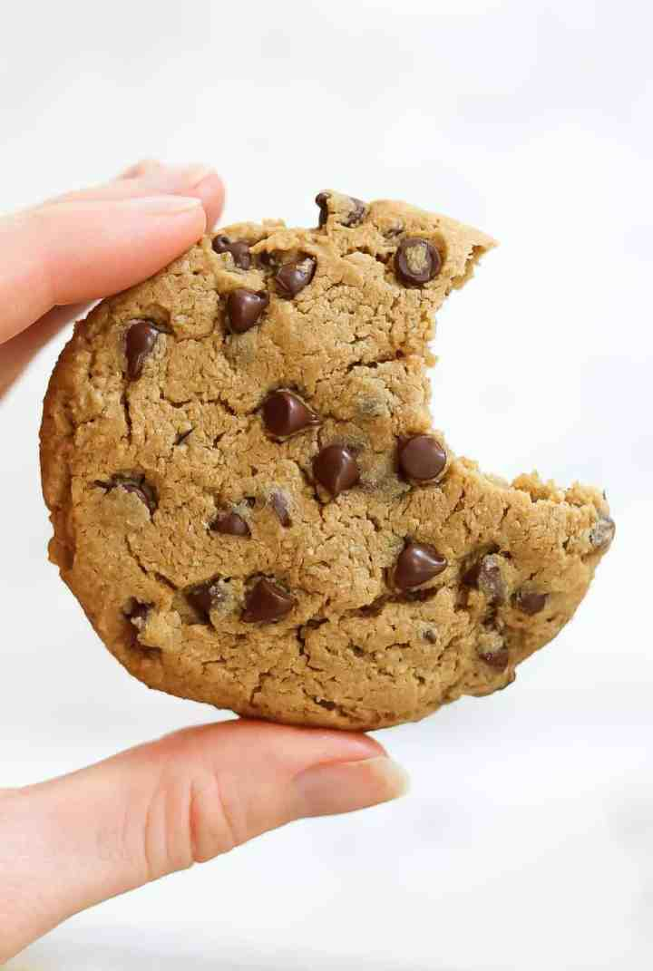 Holding a chocolate chip cookie with one bite taken out.