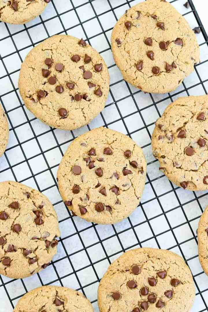 A bunch of healthy chocolate chip cookies on a black cooling rack.