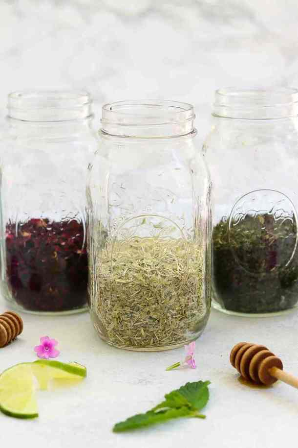Three large mason jars with herbs filled half way up for the herbal infusion.