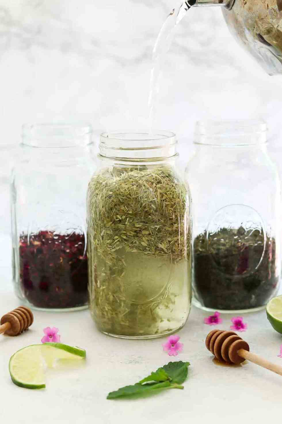 Pouring water in a jar filled with herbs.