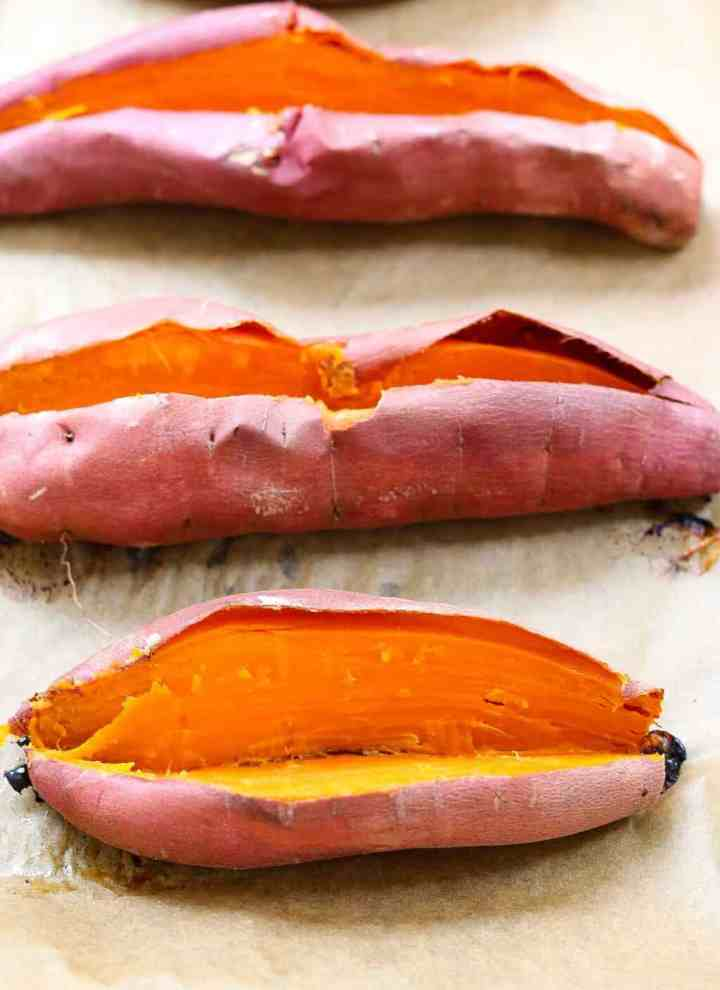 Three baked sweet potatoes on a tray with parchment paper.