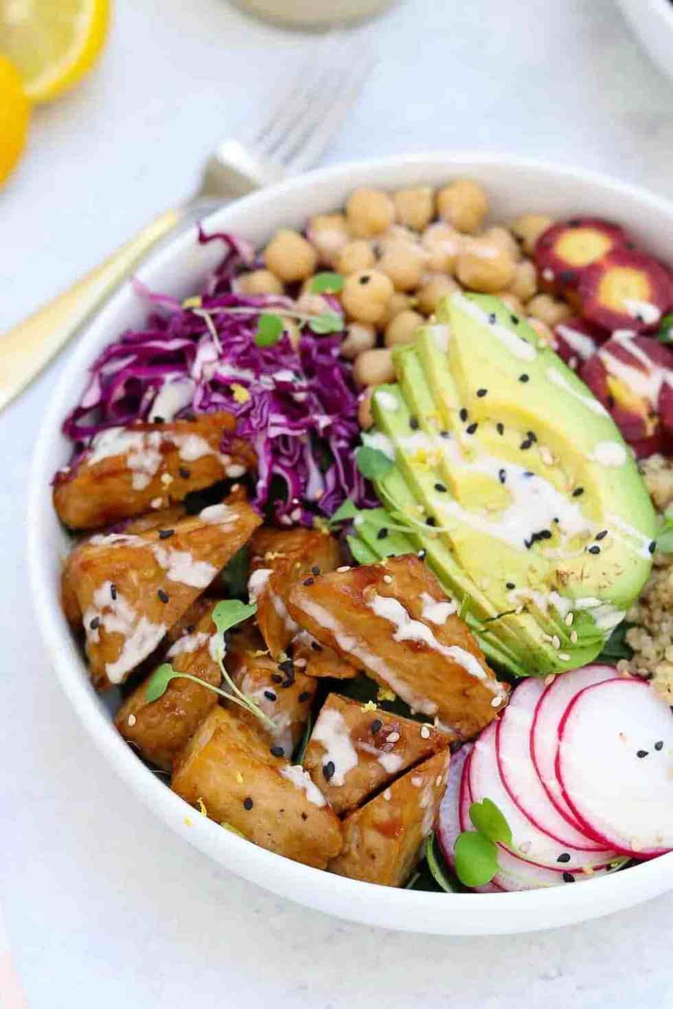 Up close image of buddha bowl with tempeh in a white bowl and orange tahini dressing on top.