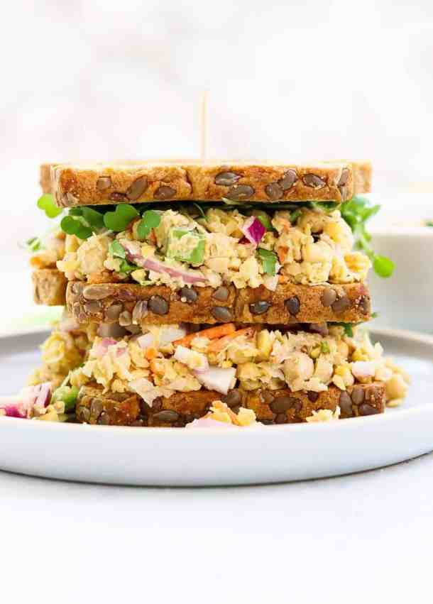 Chickpea salad sandwich with three pieces of bread on a small blue plate.
