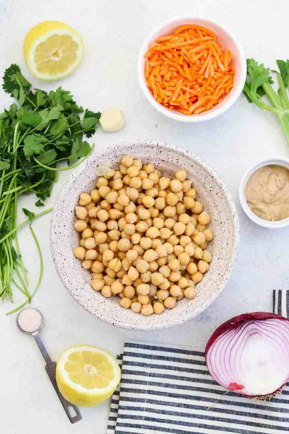 Ingredients for the chickpea salad arranged on a white backdrop.