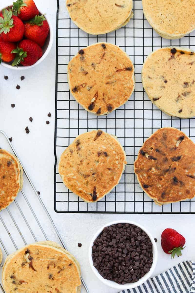 Chocolate chip pancake recipe drying on a black cooling rack.