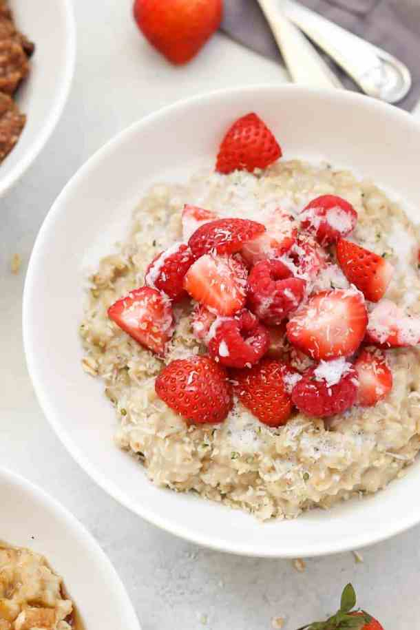 Berries and cream oatmeal in a white bowl.
