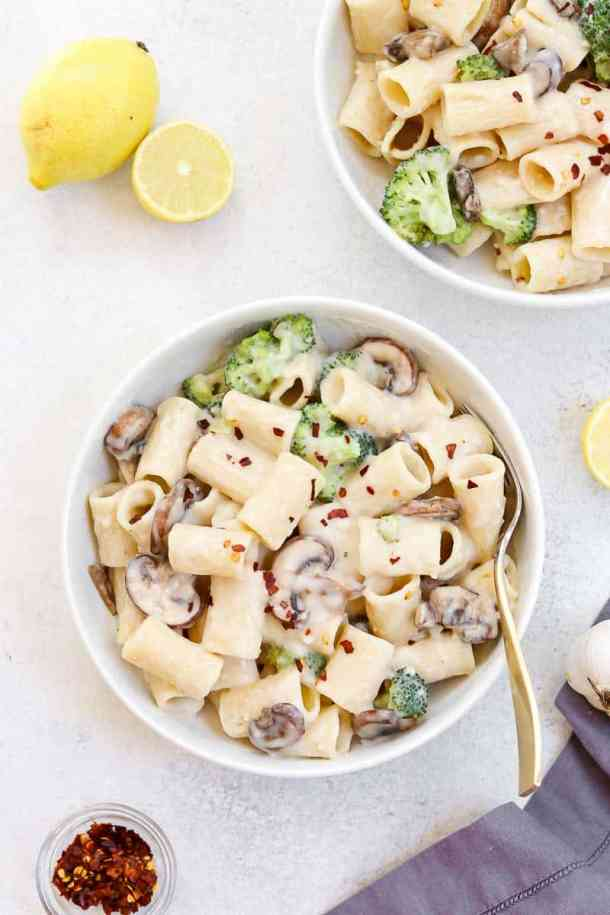Two bowls of cream sauce with rigatoni and lemon.