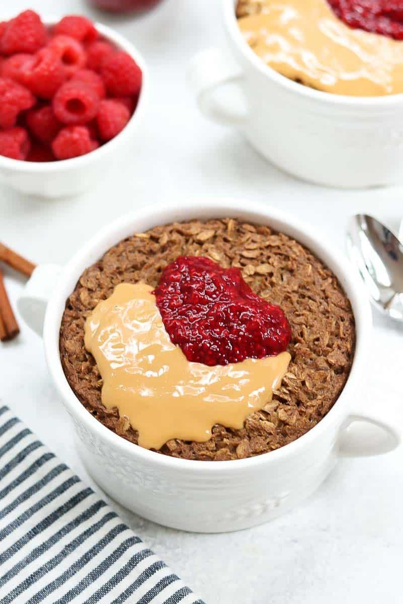 Healthy baked oatmeal recipe in a white bowl with jam and peanut butter.