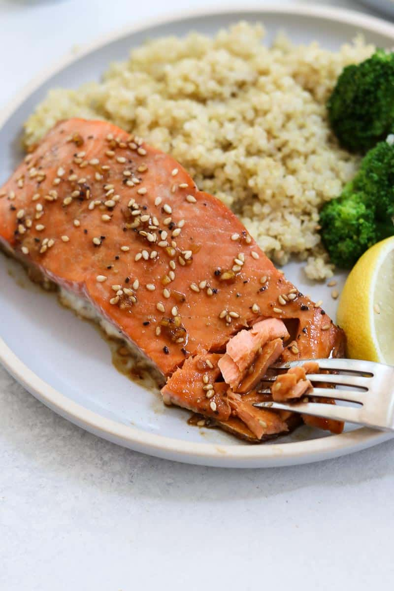 Maple glazed salmon on a blue plate with a bite taken out.