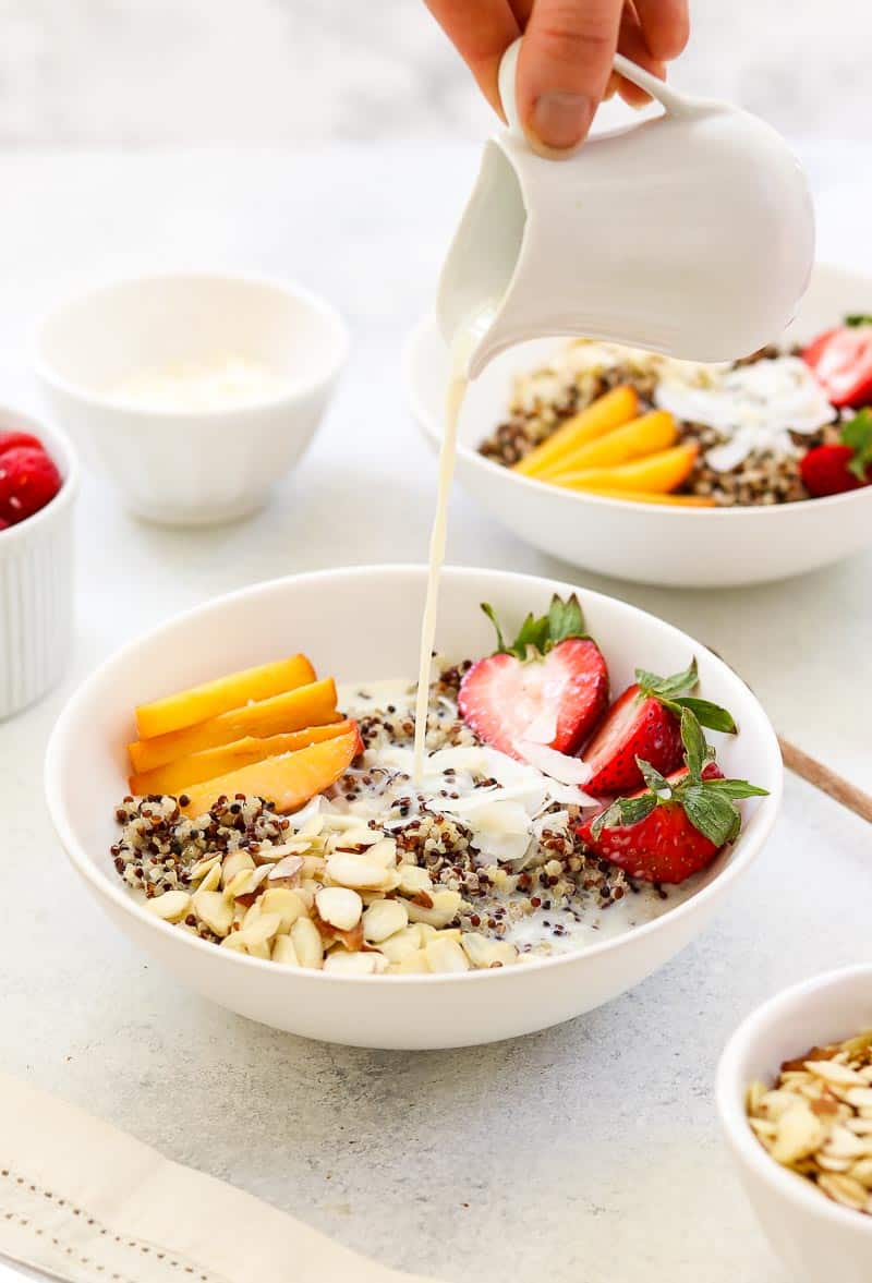 Quinoa breakfast bowl with milk poured on top.
