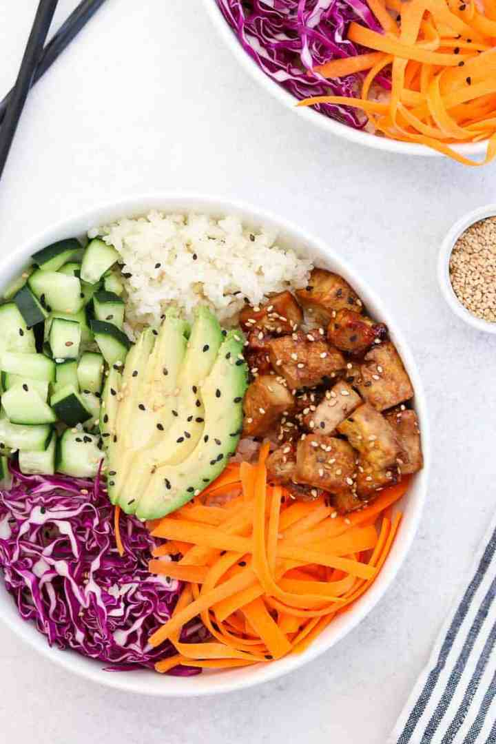 Sesame tofu and sushi bowl in a white bowl with sesame seeds sprinkled on top.